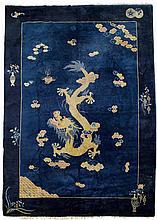 BLAUGRUNDIGER DRACHEN-TEPPICH. China, ca. 1920, 360x275 cm.Wolle. Im Zentrum wendet ein gelber, fünfklauiger Drachen den Kopf nach dem geflammten Juwel, er befindet sich zwischen locker gesetzten Wölkchen. Abgeschlossen wird der Dekor durch einen
