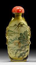 SNUFFBOTTLE MIT INNENMALEREI. China, H 7,3 cm.Ovoid, mit Maskarons auf den abfallenden Schulten, auf breitem Fussring. Transparentes, hellgelbes Glas mit Innemalerei einer Landschaft. Korallenstopper.