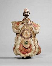 PUPPE. China, um 1900, H 40,5 cm.Stoff, Holz, Farbe, Lack und Pelz. Einen bärtigen, grimmigen Mann darstellend. Die Glieder beweglich, das Gewand bestickt. Altersspuren.
