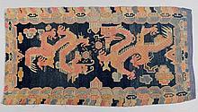 SATTELTEPPICH. Tibet, alt, 165x88 cm.Wolle. Rechteckige Form. Zwei rote Drachen auf blauem Grund umgeben von einer Wolkenbordüre. Verblasst.