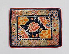 ZWEIERSET SATTELTEPPICHE. Tibet, alt, 69x57 cm u. 139x58 cm.Wolle. Je ein Lotosmotiv in zentraler rechteckiger Kartusche. Ein Teppich ist rechteckig, der andere zweiteilig und durch ein graues Stoffband verbunden.