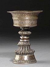 KLEINE BUTTERLAMPE. Tibet, alt, 11,7 cm.Getriebenes Silber, Kupferring. Leicht ausschwingende Schale mit eingraviertem floralen Dekor, über einem durchbrochen gearbeiteten Nodus, auf einem hohen Fuss mit Doppellotosblätterkranz.
