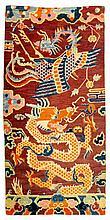 SATTELTEPPICH. Tibet, alt, 170x82 cm.Wolle. Weinroter Fond mit Dekor in blau, orange, pink und beige. Drache und Phönix zwischen Wolken. Die eine Bordüre besteht aus Wolken, die andere aus Blumen und Gartenfelsen. Farben etwas verbleicht.