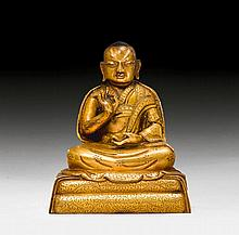 A FINE GILT COPPER FIGURE OF A MONK.