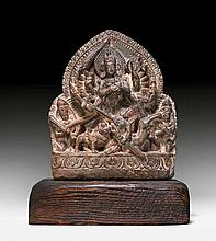 A DARK GREY STONE STELE OF DURGA SLAYING THE