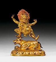 A GILT BRONZE FIGURE OF YAMA STANDING ON A BULL.