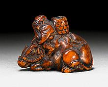 A BOXWOOD NETSUKE OF A BOY ON A RECUMBENT OX AFTER