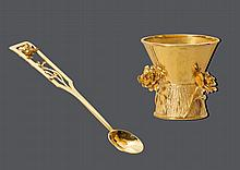 GOLD-EIERBECHER MIT LÖFFEL, um 1950.Gelbgold 750, 68g.Dekorativer Eierbecher verziert mit 3 applizierten, plastisch gestalteten Rosen und strukturiertem Fuss. H 4,5 cm. Dazu passender kleiner Löffel mit durchbrochen gearbeitetem Griff und 1
