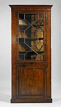 ECKVITRINE, George III, England, Ende 18. Jh.Mahagoni. Dreieckiger Korpus mit geradem Kranz und gerader Sockelleiste. Front mit verglaster, geometrisch versprosster Türe über kassettierter Türe. 95x40x221 cm. 2 Schlüssel. 1 Glas zu ersetzen.