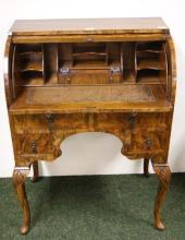 A 1920s walnut barrel-front bonheur-du-jour with fitted interior