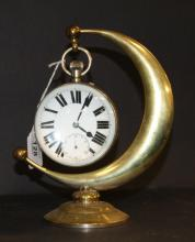 A 20th century desk clock of enlarged pocket watch form, with a crescent stand in brass. The circular dial has Roman numerals and displays a subsidiary seconds dial.