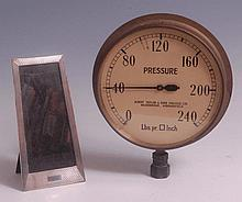 A 1930s brass circular pressure gauge, the enamel