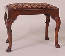 An early 18th century walnut stool, having a later