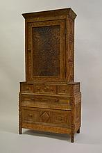 Unusual American Tramp Art side cabinet with all-over chip carved decoration, the moulded cornice above a panelled door with drawers below raised on bobbin supports
