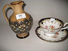 Royal Doulton stoneware jug with stylised floral decoration together with a 19th Century floral and gilt decorated cup and saucer