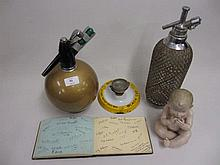 Two mid 20th Century soda siphons, an enamel advertising ashtray incorporating a dice shaker, a bisque piano doll figure and a small album of autographs
