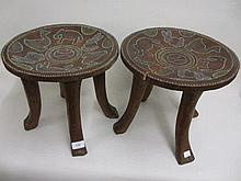Pair of African circular bead inset stools decorated with figures of animals, on four splay supports (one with crack to top)