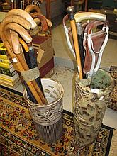 Two pottery stick stands containing a quantity of walking canes, walking sticks and shooting sticks