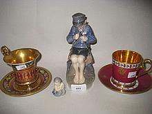 Royal Copenhagen figure of a boy whittling a stick, another of a mermaid, Continental figure of a dog and two Continental porcelain cabinet cups and saucers