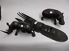 African carved hardwood wall mask and a carved wooden figure of a hippopotamus and a rhinoceros