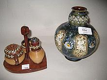 Small Doulton Lambeth baluster form vase decorated with daisies on a mottled ground (chip to rim) together with a Royal Doulton stoneware three piece condiment set on an associated wooden stand