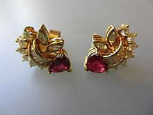 Pair of modern yellow metal diamond and heart shaped ruby set ear studs of stylised floral design
