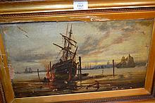 19th Century English school, oil on canvas, estuary scene with a beached hulk to the foreground (damages to picture and frame), indistinctly signed, 9.5ins x 17ins