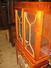 Reproduction yew wood display cabinet on stand with two glazed doors above six small drawers on square tapering supports with undertier