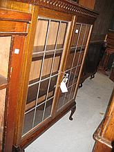 Oak bookcase with two leaded glass doors on cabriole supports together with another similar smaller bookcase