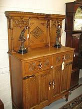 Gothic revival carved oak side cabinet, the canopy back with tracery panels supported by turned columns, the base with two drawers and two panelled doors decorated with further tracery work and linen fold carving raised on square cut supports with
