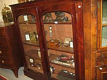 19th Century mahogany bookcase having moulded cornice above two arched glazed doors enclosing adjustable shelves on plinth base