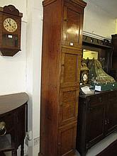 Early 20th Century oak tall narrow storage cabinet with a moulded cornice above four panelled doors enclosing a partially fitted interior
