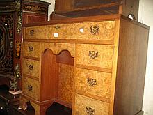 Mid 20th Century burr walnut kneehole desk with a plain top above a central cupboard surrounded by an arrangement of various drawers with brass handles and bracket feet