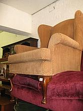 Modern upholstered wing armchair with brown moquette upholstery on cabriole front supports