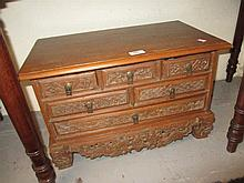 Korean lacquer table cabinet, the shaped top above an arrangement of small drawers and two cupboard doors on bracket feet