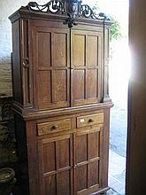 Oak side cabinet with carved and pierced scroll work pediment above a pair of panelled doors, two drawers and two further panelled  doors