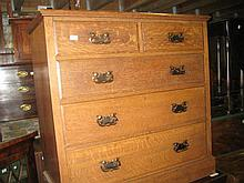 Late Victorian oak chest of two short and three long graduated drawers with oxidised copper handles above a plinth base, bearing the retail label of Maple and Co.