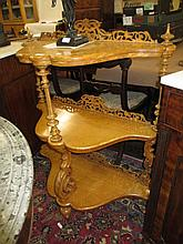 Victorian birds eye maple serpentine shaped three tier etagere with pierced fretwork back and turned uprights, on baluster turned supports with brass caps and casters
