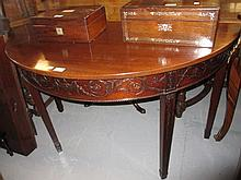 19th Century mahogany D-shaped side table in George III style, the frieze and square tapering supports carved in shallow relief with urns, floral scrolls and swags