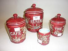 Four 20th Century pottery enamel floral decorated canisters, three with covers