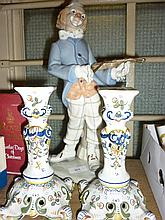 Pair of modern floral decorated Faience candlesticks and a porcelain figure of a clown playing a violin