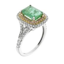 AN EMERALD AND DIAMOND CLUSTER RING: centring a step cut emerald (chips around a claw) to surround and split shoulders set round bri...