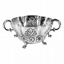 A George III silver double handled cup with embossed decoration and raised on paw feet. Height: 6cm.