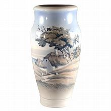 A large Royal Copenhagen vase painted with a landscape of a beachside house,