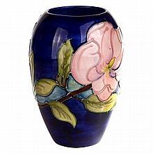 A Moorcroft Magnolia pattern vase, signed to base.