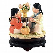 A Chinese Republic carved and coloured ivory group of children pulling a cart of two seated girls with peach and pumpkin and stand