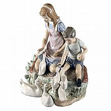 A Lladro figure of a girl and her brother feeding ducks, printed and impressed marks to base.