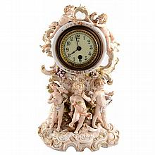 A Rudolstadt rococo style porcelain clock case with a movement by HAC with floral and putti decoration.