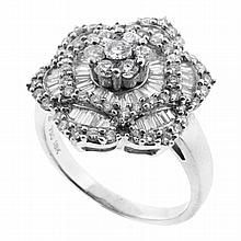 AN 18CT WHITE GOLD DIAMOND CLUSTER RING; floral cluster set with sixty seven round brilliant and fifty seven tapered baguette diamon...