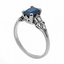 AN 18CT WHITE GOLD DIAMOND AND STONE SET RING; centring a synthetic blue sapphire adjacent to 4 single cut shoulder diamonds. Size m...